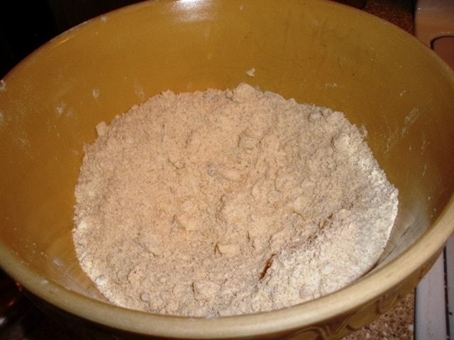 A bowl with flour in it with pieces of butter rubbed in to make pie dough.