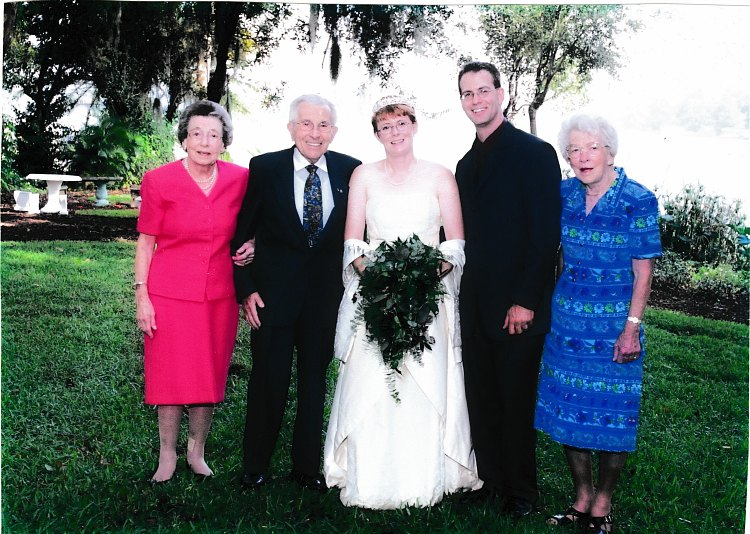 A bride and groom standing in a grass field with their grandparents.