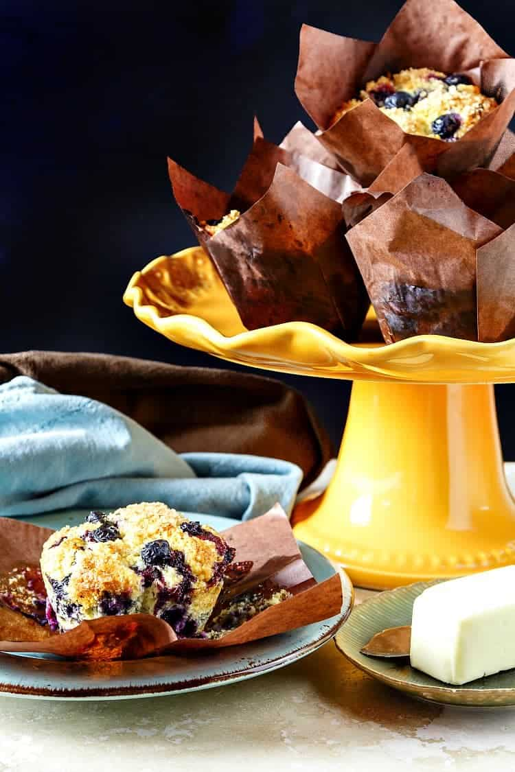 An orange cake stand piled with blueberry muffins in brown paper wrappers with one muffin on a plate.