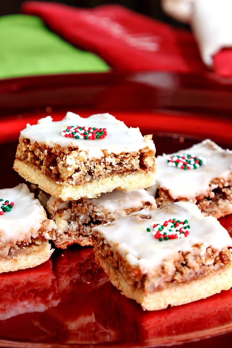Square angel slices bar cookies with white icing and some Christmas sprinkles on top stacked on a red plate.