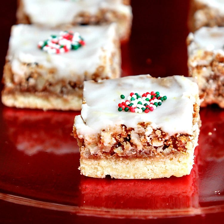A close up of a pecan angel slice showing lemon glaze on top, red, white, green sprinkles, all on a red plate.