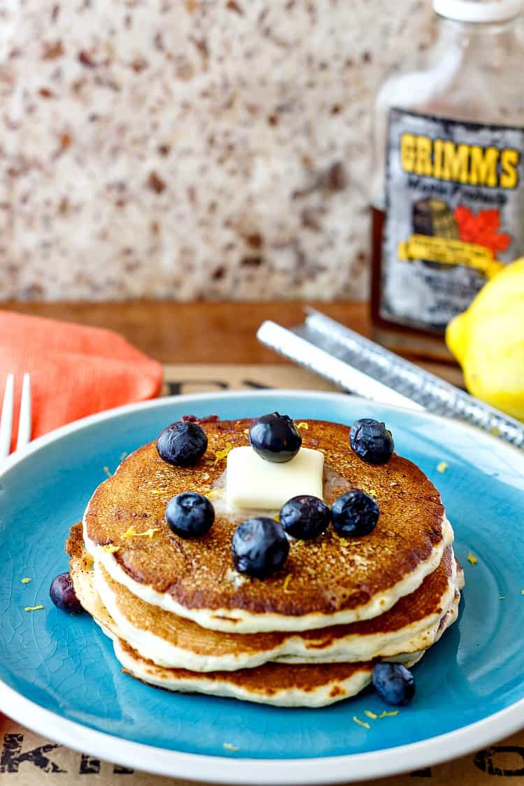 A stack of 3 pancakes for one on a blue plate with a pat of butter and fresh blueberries.