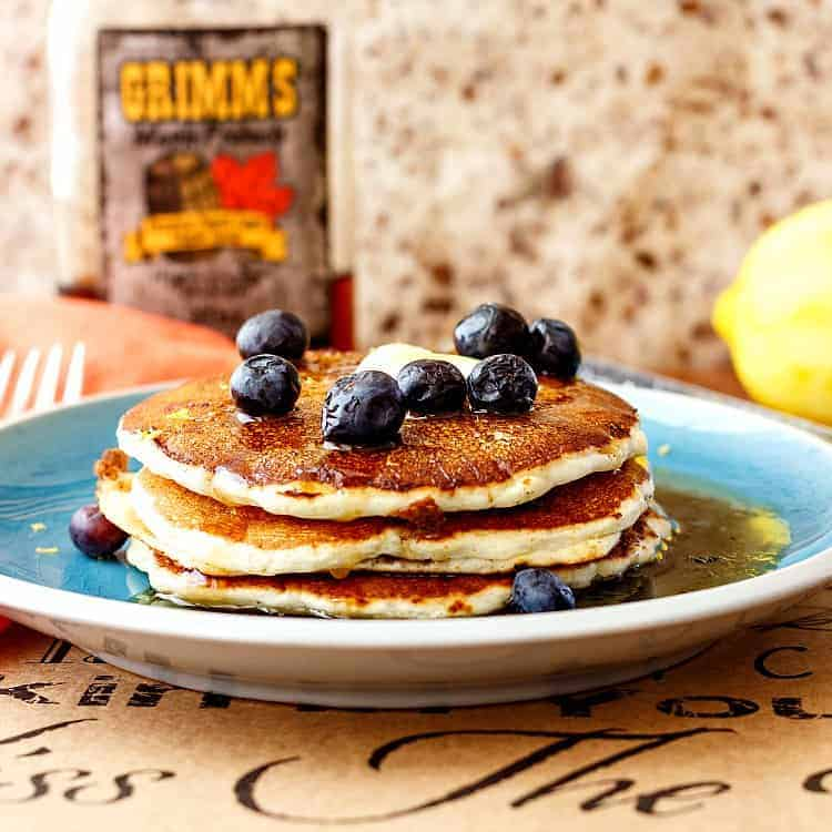 A close shot of stack of three pancakes on a blue plate topped with a pat of butter and fresh blueberries.