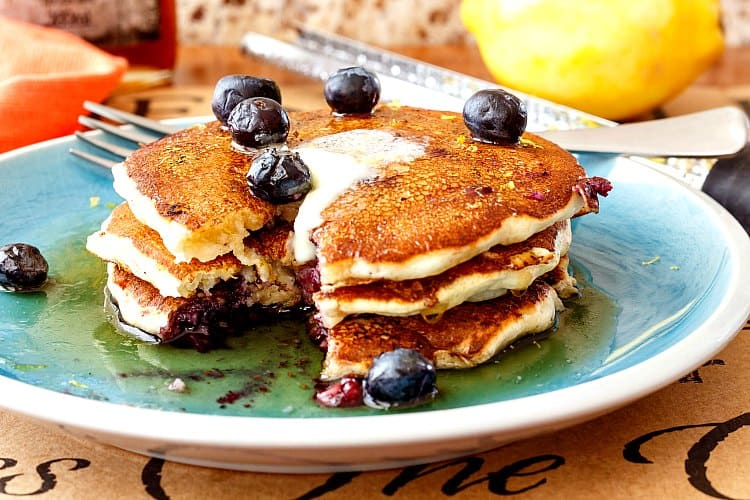 A stack of 3 pancakes with a bite cut out. Melted butter, syrup and fresh blueberries on top.