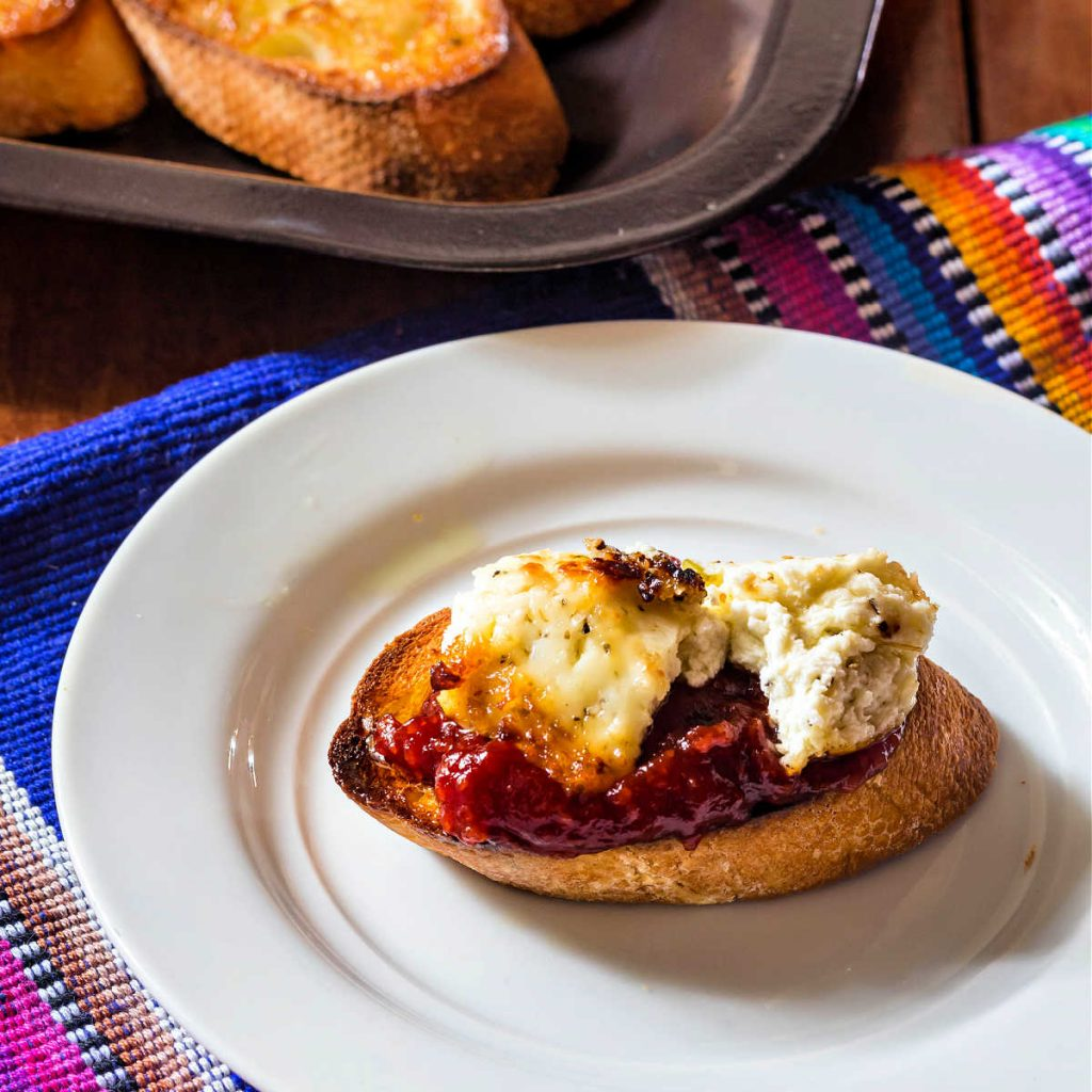 Crostini topped with tomato jam and goat cheese on a white plate.