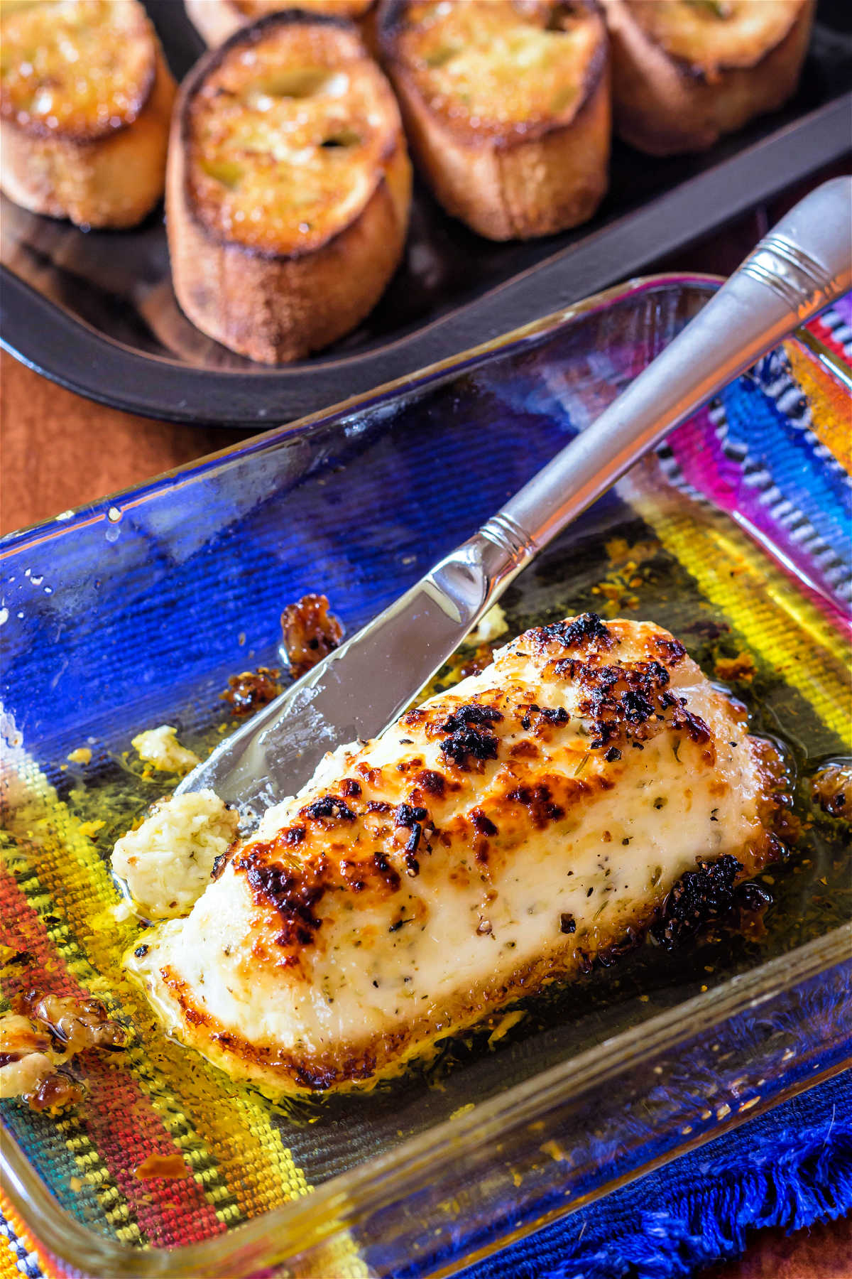 A glass baking dish containing a log of broiled goat cheese swimming in olive oil. In the background is a tray of toasted crostini.