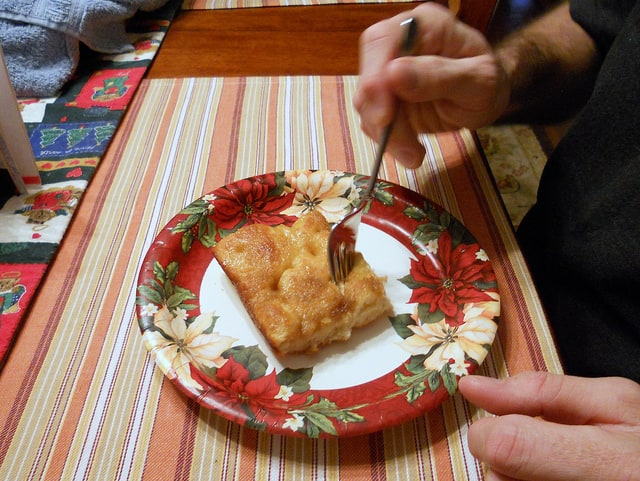 A slice of Moravian sugar cake on a holiday decorated paper plate with a fork in it, ready to take a bite.