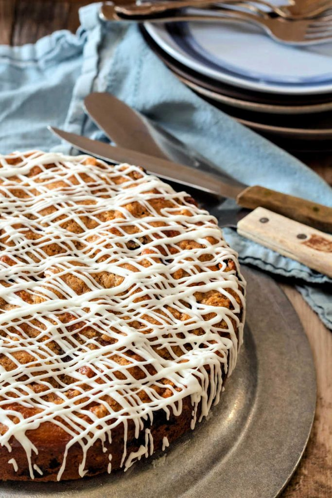 Vertical image of browned butter blueberry buckle on a pewter tray with a blue napkin and a cake server.