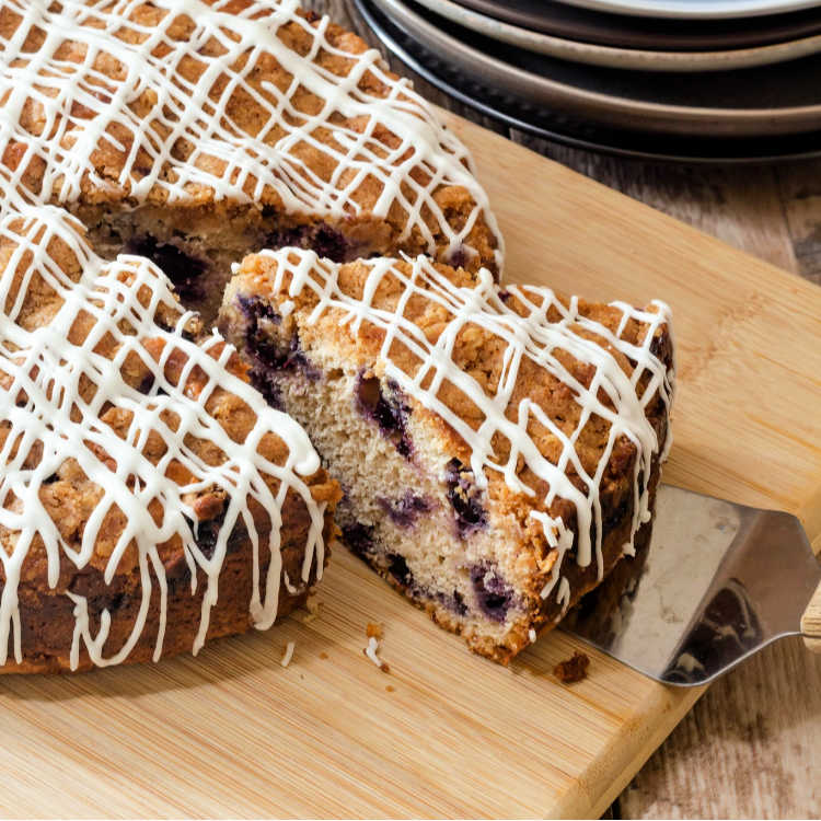 Brown butter blueberry coffee cake with glaze drizzled on it on a cutting board with one slice cut out of it.