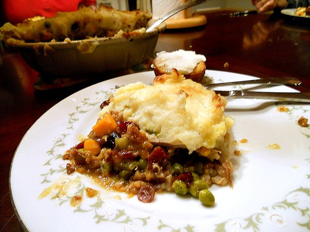 A slice of thanksgiving turkey shepherd's pie with stuffing crust on a white plate along with a buttered corn muffin.