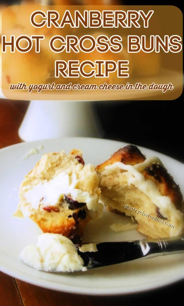 """Cut hot cross bun on a plate. Text reads """"cranberry hot cross buns recipe with yogurt and cream cheese in the dough."""""""