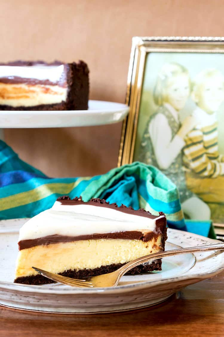 A slice of chocolate cheesecake pie and a fork on a plate with the rest of the pie on a pedestal and a photo of my brother and me in the background.