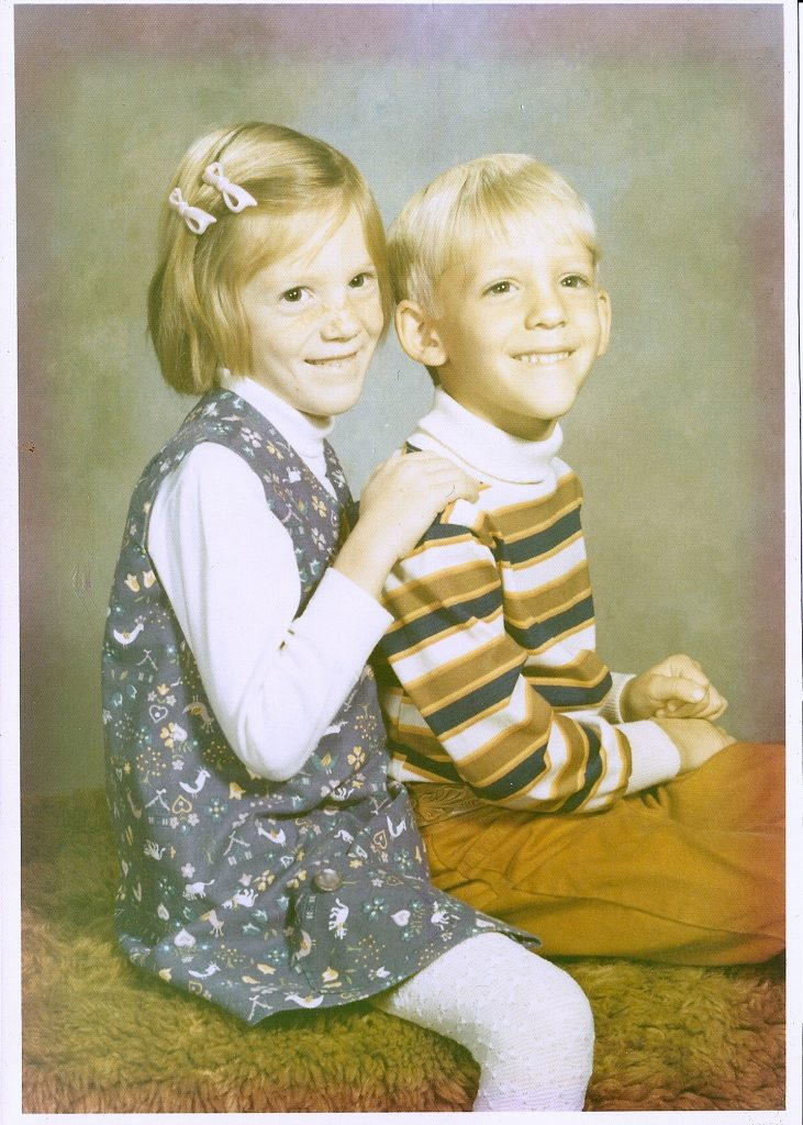 A photo of a girl and a boy sitting together on a carpet-covered bench. Taken in 1971.