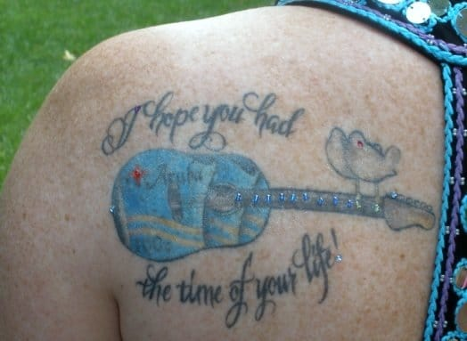 """Memorial Tattoo for Greg of a guitar and text reading """"I hope you had the time of your life!""""."""
