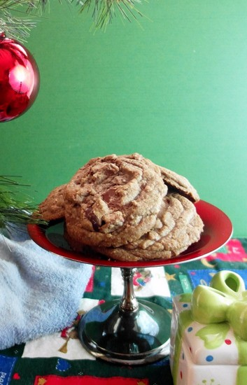A footed serving dish filled Brown Butter Toffee Chocolate Chip Cookies next to a Christmas tree.