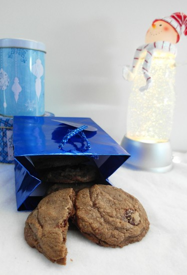 A whole and one half of Brown Butter Toffee Chocolate Chip Cookies next to a gift bag ready for holiday giving.