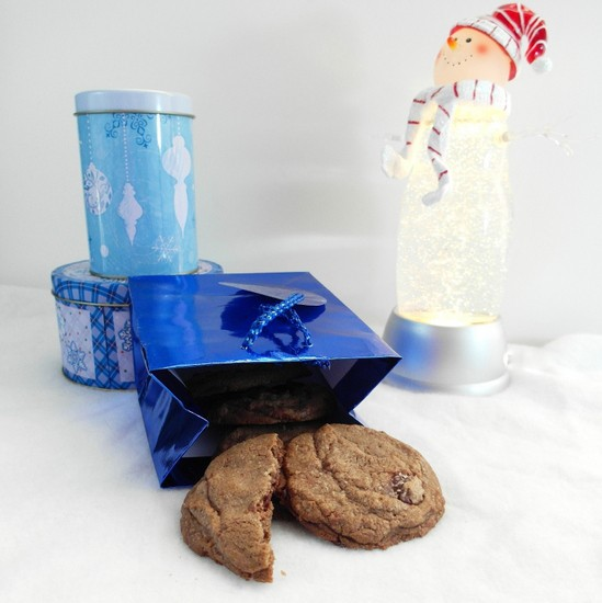 A blue shiny gift bag with Brown Butter Toffee Chocolate Chip Cookies spilling out. Cookie tins are in the background as is a light up snowman.