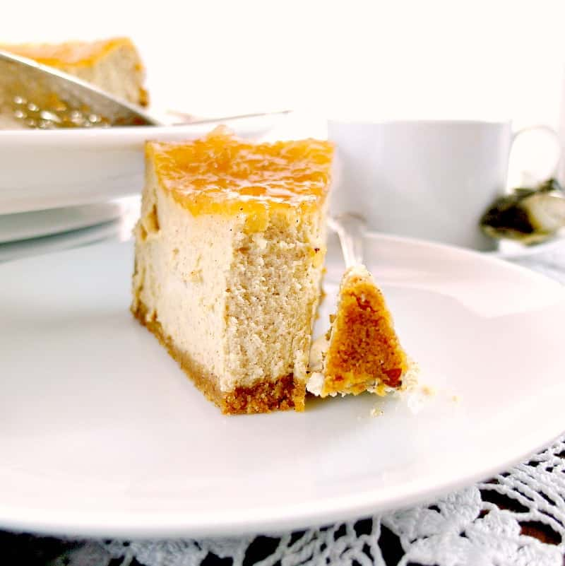 A slice of cinnamon buttermilk cheesecake with apple pie topping on it on a white plate with a bite on a fork.