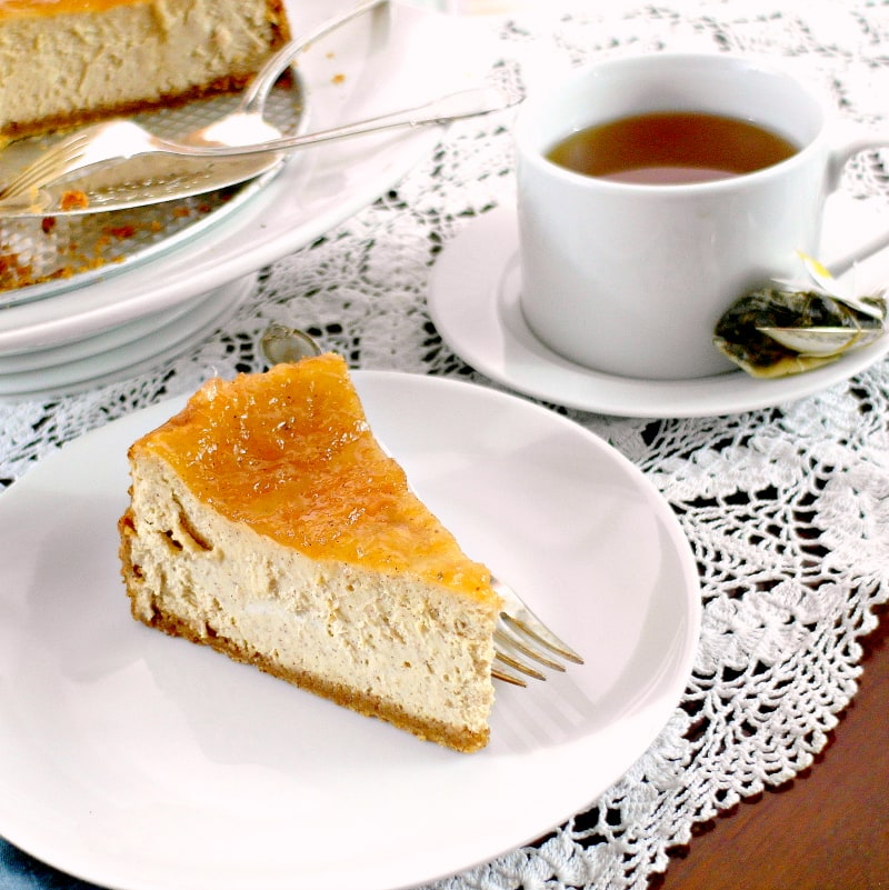 A slice of cinnamon buttermilk cheesecake on a white plate with a cup of tea.