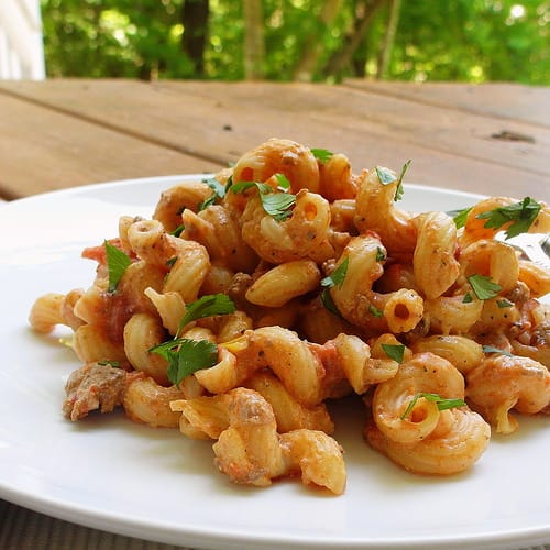 A white plate with serving of creamy cavatappi pasta.