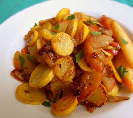 Zephyr Squash, Onion and Apple Sauté piled in the center of a white plate.