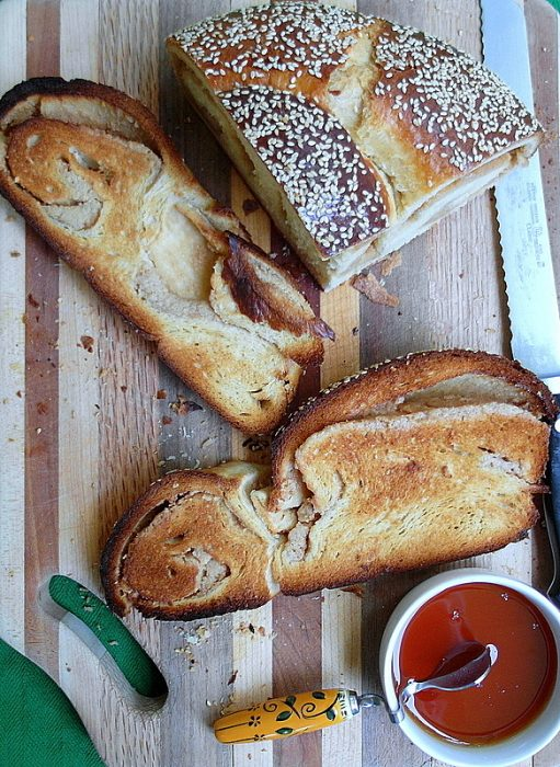 overhead shot of a bread board with sliced and toasted challah bread with sesame seess on top