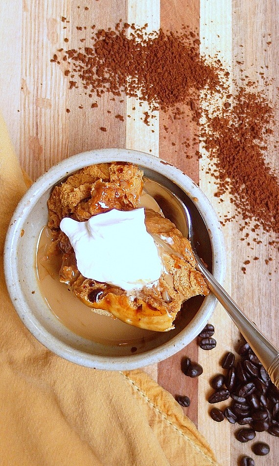 Overhead shot of caramel coffee mousse in an earthenware bowl with whipped cream on top. Ground coffee is sprinkled to the side and coffee beans are on the other side.