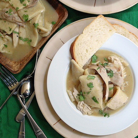 Chicken and slick dumplings sprinkled with parsley and served with homemade white bread.