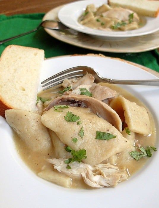close up shot of chicken & dumplings sprinkled with parsley