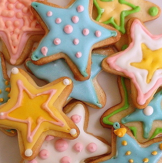 Decorated shortbread cookies cut out in star shapes and decorated in different pastel colors.