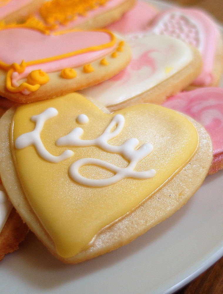 """Closeup of a decorated heart-shaped cookie with pale yellow frosting and white cursive writing that spells """"Lily."""""""