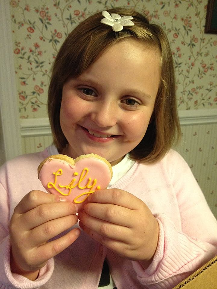 """A little girl with brown hair holding a heart shaped cookie decorated in pink frosting with """"Lily"""" written in yellow."""