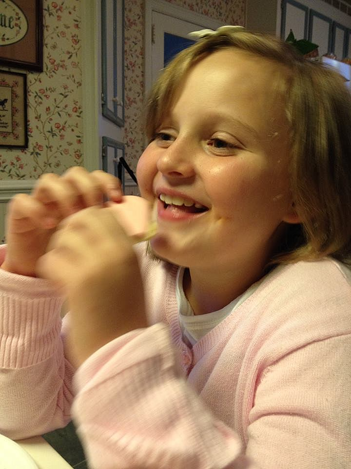 A smiling girl eating a sugar cookie.