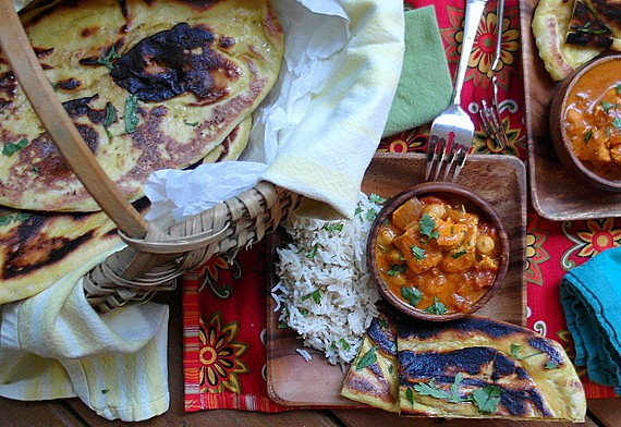 Kashmiri Naan and an Indian meal on a table. Naan loaves are in a rattan basket. Basmati rice is on a square wooden plate. An indivdiual sized serving bowl is filled with a stew that is predominantly red and chunky, topped with chopped fresh herbs. There is a colorful red and yellow placemat under wooden plate.
