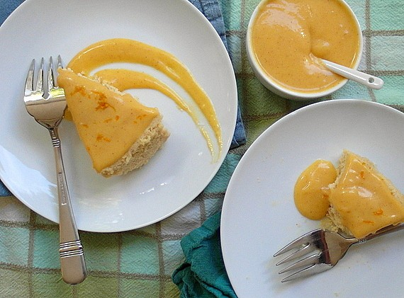 2 plates with pumpkin butter Japanese cheesecake each on white plates. Both have forks. One is missing a bite. A small ramekin of Pumpkin Spice Tangerine Curd is next to the plates with a spoon it it ready for serving. Both slices have curd on top.