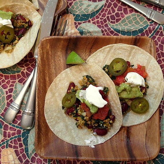 Veggie Oat taco mince on two corn tortillas with jalapenos, guacamole, and sour cream garnish. They are plated on wooden plates and there is a wedge of lime garnish.