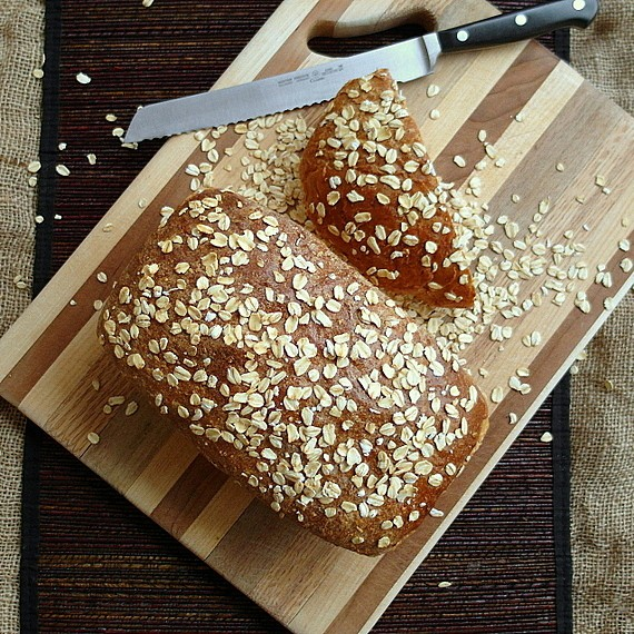 A loaf of old neighborhood oatmeal porter beer bread with oatmeal scattered on top.