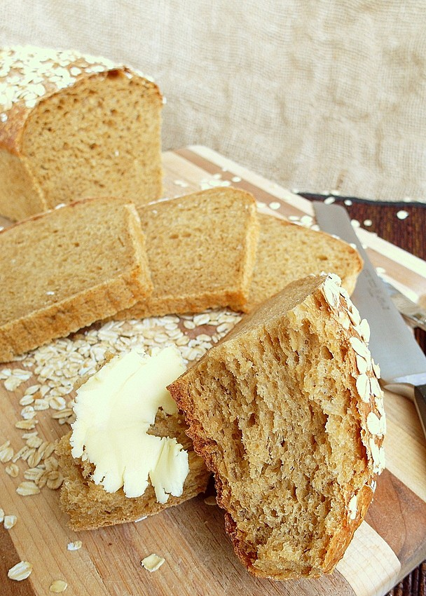 Sliced loaf of oatmeal beer bread. One slice has butter on it.