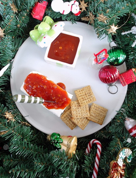 Overhead shot of a block of cream cheese with red sauce poured over it, a container and Triscuits.