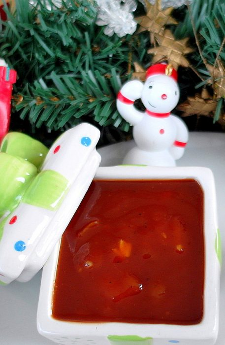 A square holiday themed container of sweet and sour red sauce.