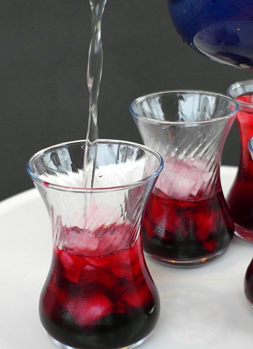 Hibiscus rose sharbat pouring into Turkish clear glasses. Beverage is deep red over ice.