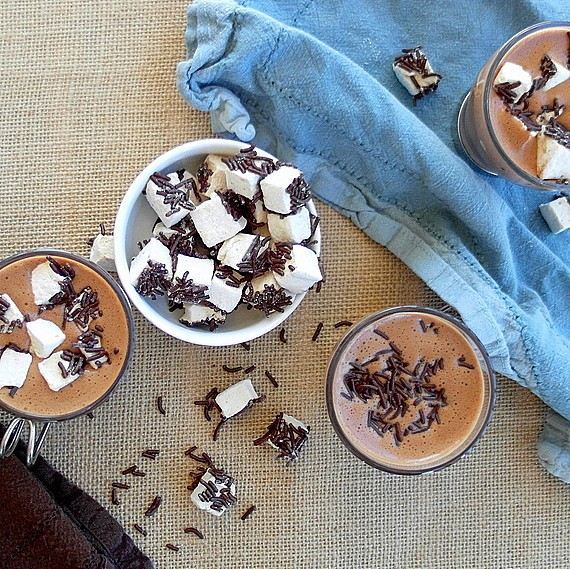 Overhead view of 4 mugs. One mug of mini marshmallows with a coating of chocolate jimmies. The other mug has hot chocolate custard in it and a sprinkle of chocolate jimmies on top. The other two mugs have hot chocolate and jimmie covered mini-marshmallows on top. All are on a table covered with burlap and one is on a lightly wrinkled blue chamois napkin. There are some jimmies and marshmallows sprinkled around.
