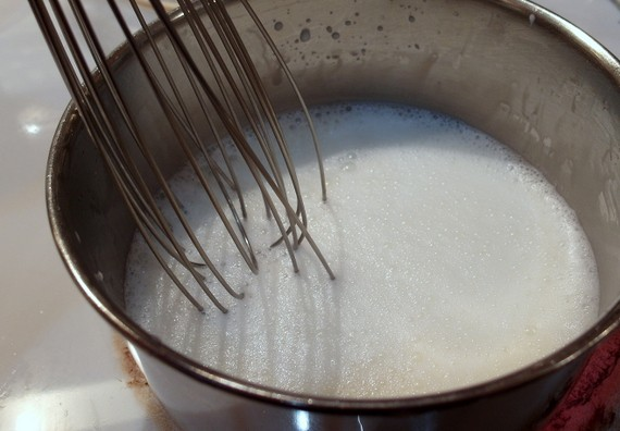 A pan of milk with a whisk in it and many tiny bubbles on the top.