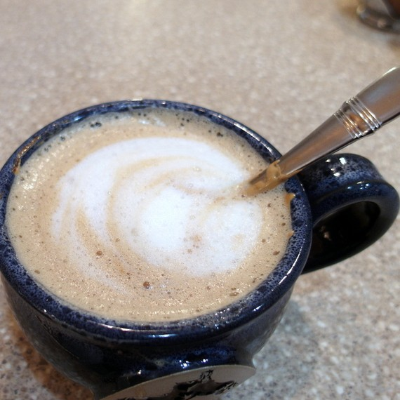 An earthenware blue mug of beaten coffee or Indian cappuccino with a spoon in it.