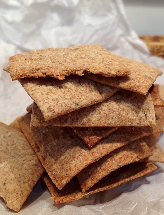 A stack of rye crackers on parchment paper.