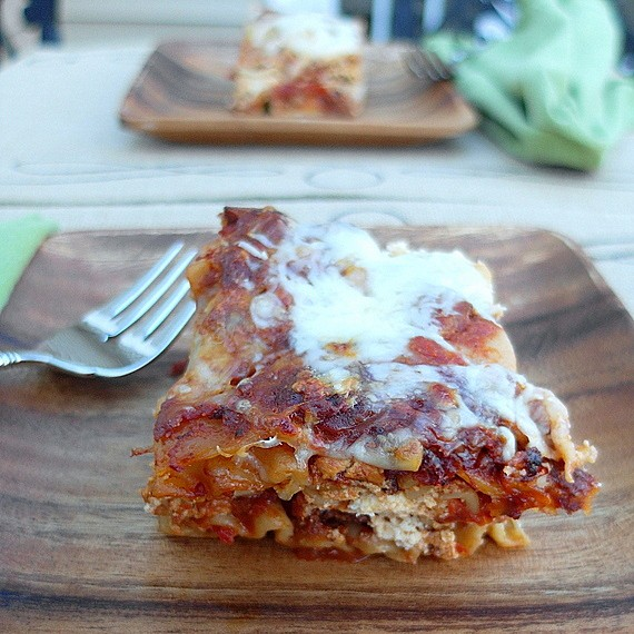 Side view of one serving of five cheese hot Italian sausage lasagna on a wooden plate. Another serving on a wooden plate is in the background.