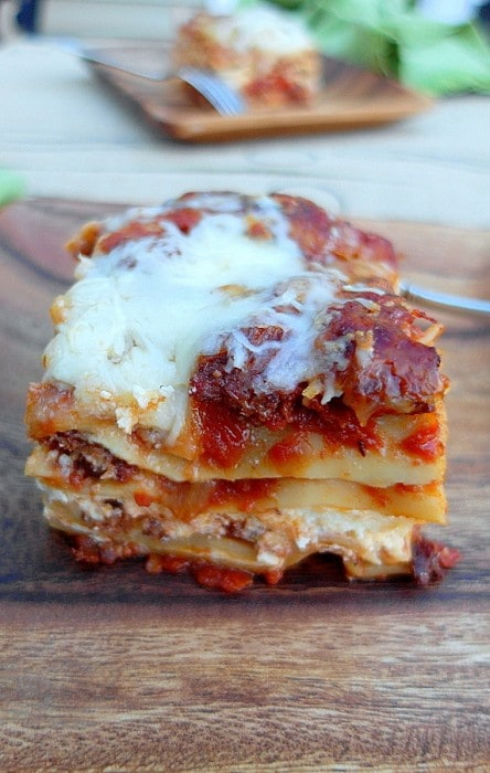 One serving of five cheese hot Italian sausage lasagna on a wooden plate. The side view shows the layers and melted cheese and the tomato sauce.