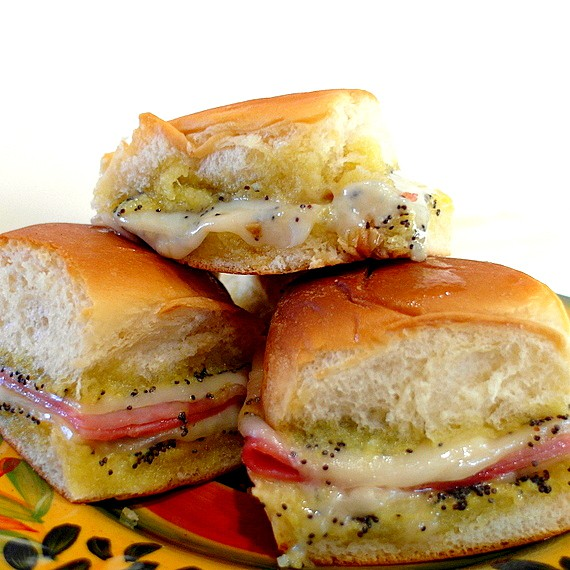 Close up of a pile of ham and cheese sliders on a plate.