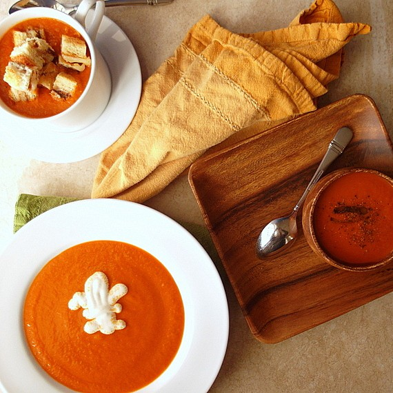 A mug of tomato soup with grilled cheese croutons, a small wooden bowl and a white rimmed bowl with tomato soup.