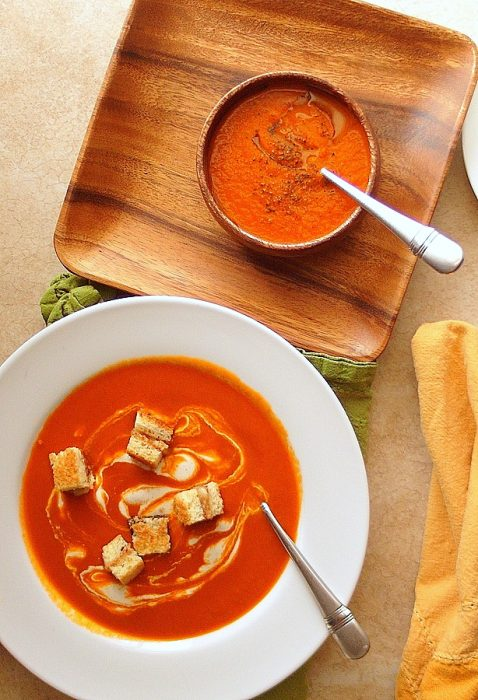 Overhead shot of Cajun spicy tomato soup in two different bowls, one with bacon and Swiss grilled cheese croutons.